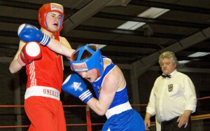 Trading leather: Tralee boxers, Paddy Burke (left) and Michael Coffey getting stuck in under the watchful eye of referee, John O'Regan at the Sliabh Luachra Boxing Club in Castleisland last February. ©Photograph: John Reidy