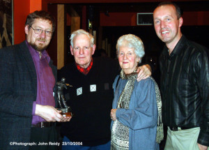 Patrick O'Keeffe Traditional Music Festival founder, Peter Browne (left) presents Paddy Cronin with the festival award for a lifetime of dedication to the music of the Sliabh Luachra region in Castleisland during the 2004 festival. Included are; Mr. Cronin's wife Connie and festival chairman, Cormac O'Mahony.  ©Photograph: John Reidy  23/10/2004