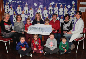 Pupils and teachers at Muire Gan Smál National School, Castleisland handing over the proceeds of their Christmas jumper day to representatives of the local branch of the Society of St. Vincent de Paul. Front: Alex Danowski, Maria Greaney, Shinora Riordan-Deery and Tadhg Nolan.  Seated from left: Mary Frances O'Shea and Martha O'Mahony, teachers; Shauna Griffin, Maura Browne, acting principal; Báithín O'Mahony, Helen O'Donoghue, St. Vincent de Paul; Marie Brosnan, former principal and Liz Galwey, St. Vincent de Paul. ©Photograph: John Reidy