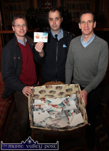 Garda Mark Bolger drawing the winning tickets in the Castleisland Traders' Association Christmas Draw at the River Island today. Included are association members, Jeremy Burke (left) and Bill Costello. ©Photograph: John Reidy