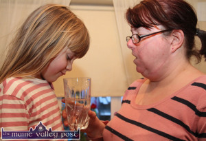 What's in it Mom ? Elaine Courtney and her daughter, Gráinne pictured with a glass on non-drinkable tap water at home in An Caisleán Mór this evening. ©Photograph: John Reidy