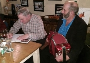 Cllr. Danny Healy Rae knocking a tune from the box as Connie O'Connell signs a copy of his book / CD set Bóthariin Na Smaointe for the colourful Kilgarvan politician.