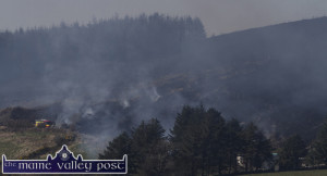 A fire brigade unit moves into position to contain the gorse fire at Knockatee with the fire blackened mountain to the right of the picture on Saturday afternoon. ©Photograph: John Reidy