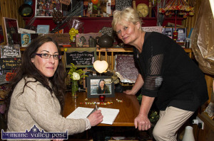 Ita Prendiville signs the Karen Buckley Book of Condolence with Kate Walsh in the Rock Library at the Slice of Life Health Food Store on Main Street earlier today. ©Photograph: John Reidy