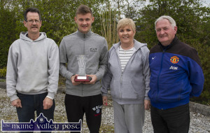 Home for the weekend: Ipswich Town's latest signing, Shane McLoughlin pictured with his parents, Eamon and Mary and his schoolboy days coach, Georgie O'Callaghan. Shane is holding the trophy presented to him by the club to mark his signing with Ipswich Town. ©Photograph: John Reidy