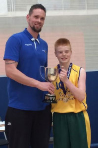 Garry O'Sullivan Captain of the St. Patrick's Basketball team being present with the All Ireland Basketball cup by Basketball Ireland official, Jason Killeen. Photograph Courtesy of St. Patrick's.