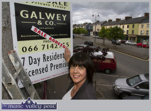 Liz Galwey of Galwey & Co. Auctioneers pasting the 'Sale Agreed' sticker on the sign at Sheila Prendiville's this evening. ©Photograph: John Reidy