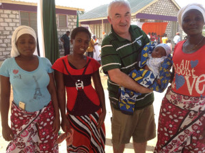 Looking suspiciously like a man out canvassing, Charile is holding the baby with his new friends in Kenya.