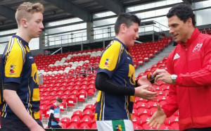 Doug Howlett of Munster presenting medals to members of St. Patrick's winning team, Padraig Fleming and Jonathan Healy.