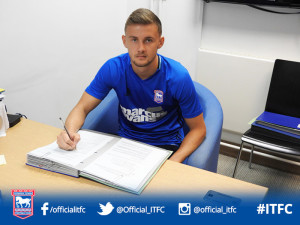 Shane McLoughlin signing the Ipswich Town contract this week.