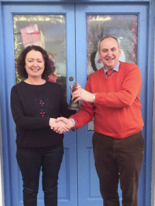 Retiring principal Denis Griffin handing over the school bell to his successor, Marina O'Connor at Scoil Naomh Charthaigh yesterday. Photograph: Scoil Naomh Charthaigh.