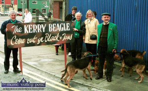 Castleisland houndsman, Anthony Cronin with his pack of Black and Tans and James O'Connor, Teresa Cronin and Sheila Mullally waiting to join in the 2002 St. Patrick's Day. The sign was painted by the late Mike Kenny after much draughting on the counter of Sheila Prendiville's Bar and Grocery. ©Photograph: John Reidy 17/3/2002